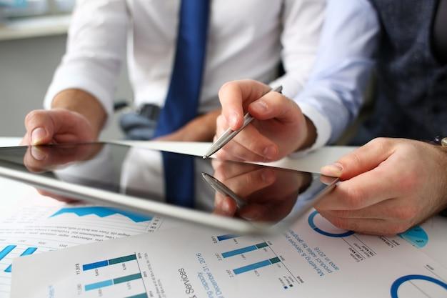 Grupo de hombres de negocios señalan con el dedo y la pluma de plata en brazos con primer plano de pc de almohadilla electrónica. gestión de datos del mercado de valores financiero trabajo banco remoto o aplicación de comercio electrónico estilo de vida moderno