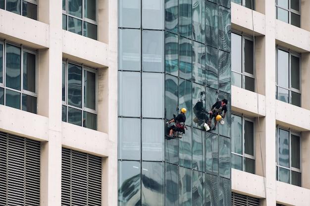 Grupo de hombres trabajadores colgando cabestrillo con la limpieza de la ventana del moderno edificio de gran altura