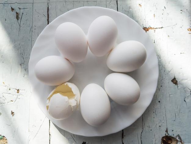Un grupo de huevos blancos y cáscaras de huevo entre ellos en una placa blanca, sobre un fondo de madera blanca