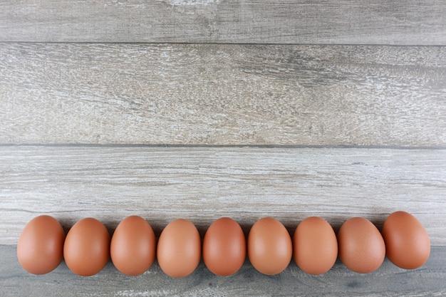 Grupo de huevos de gallina fresca de granja en el fondo de la tabla de madera vintage. imagen publicitaria concepto de comida con espacio libre.