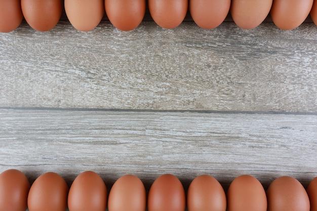 Grupo de huevos de gallina frescos de granja en mesa de madera vintage.