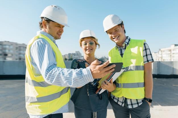 Grupo de ingenieros, constructores y arquitectos en la obra.