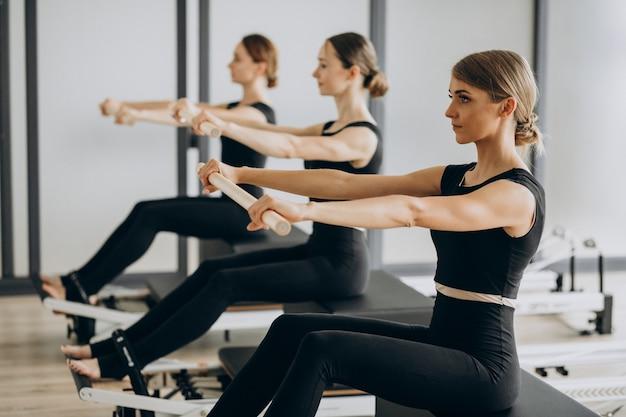 Grupo de instructores de pilates haciendo ejercicio en reformadores