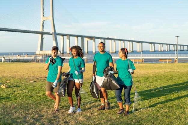 Grupo interracial de voluntarios llevando basura del césped de la ciudad