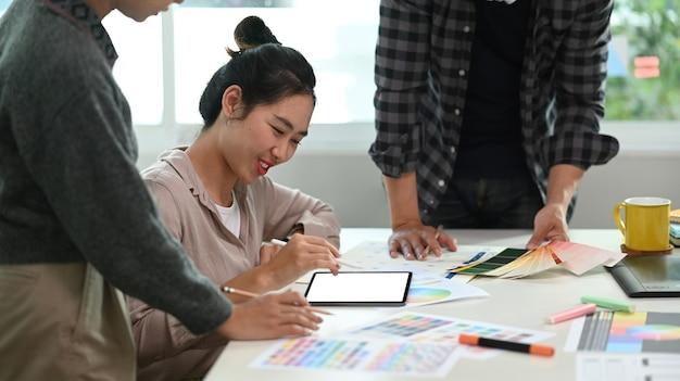 Grupo de joven diseñador asiático con tableta digital y selección de color para el nuevo producto en la oficina moderna.