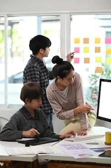 Grupo de joven diseñador discutiendo el nuevo concepto creativo para la promoción de marketing de nuevos productos en la oficina moderna.