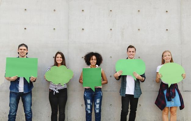 Grupo de jóvenes adultos al aire libre sosteniendo carteles vacíos copyspace pensamiento burbujas