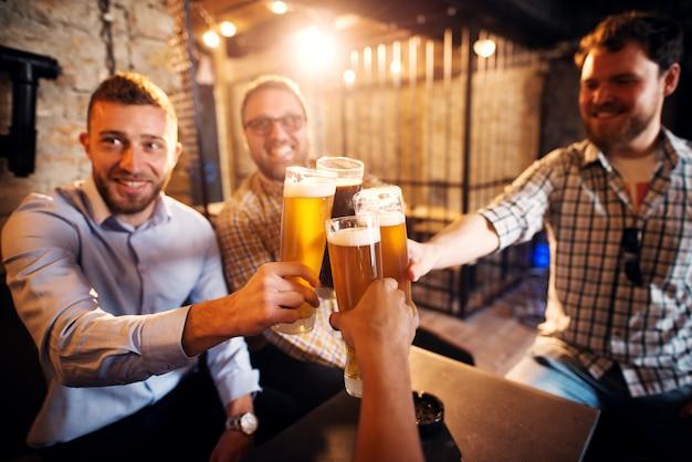 Grupo de jóvenes alegres tintineo de vasos con una cerveza en el pub soleado después del trabajo.