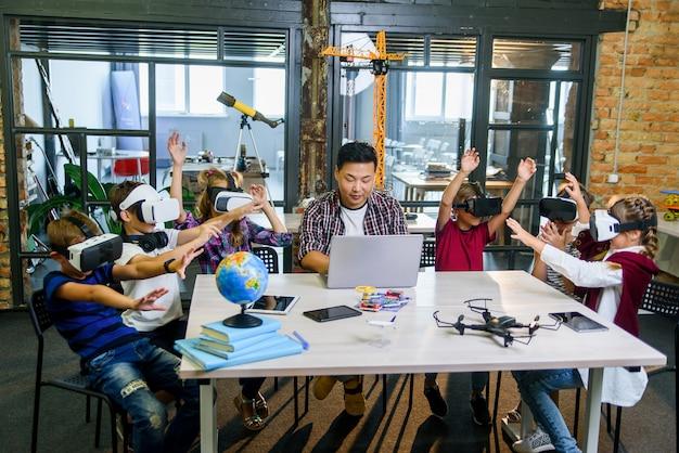 Grupo de jóvenes alumnos de primaria utilizando gafas de realidad virtual durante la clase de codificación informática.