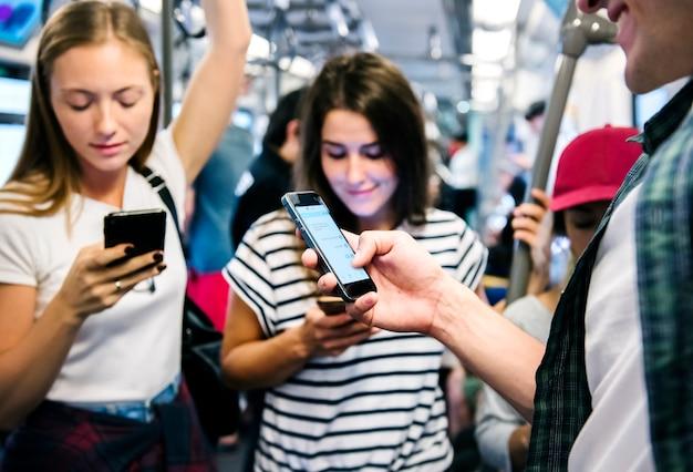 Grupo de jóvenes amigos adultos que usan teléfonos inteligentes en el metro