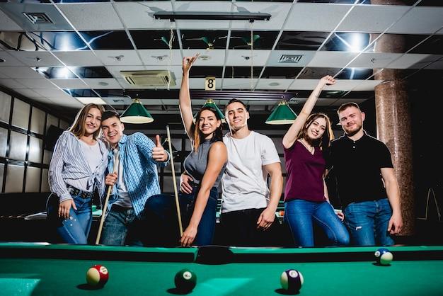 Grupo de jóvenes amigos alegres jugando billar.