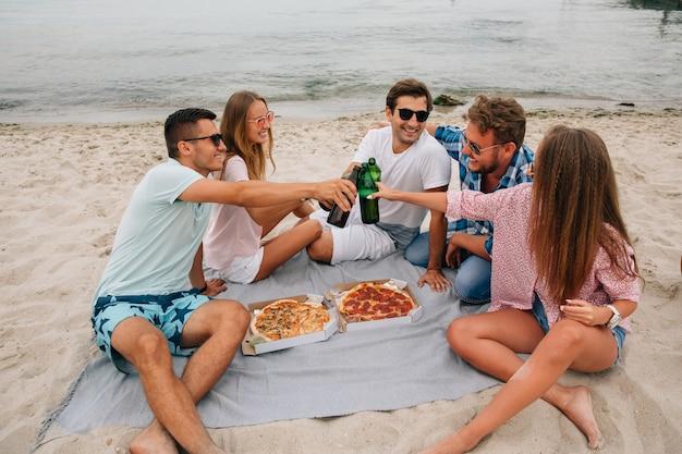 Grupo de jóvenes amigos atractivos haciendo un brindis, bebiendo cerveza con pizza