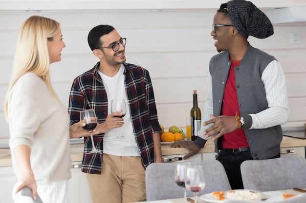 Grupo de jóvenes amigos bebiendo vino y escuchando a chico afroamericano en fiesta en casa