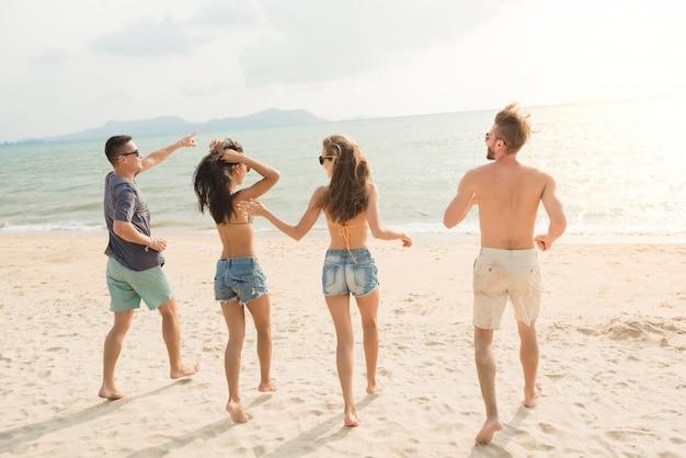 Grupo de jóvenes amigos felices corriendo desde la playa hasta el mar.