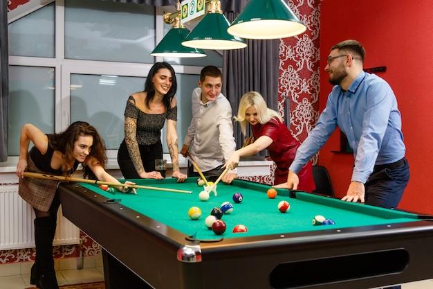 Grupo de jóvenes amigos jugando billar