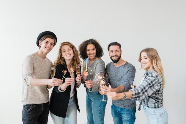 Grupo de jóvenes amigos multiculturales emocionados en ropa casual brindando con flautas de champán y sosteniendo luces de bengala