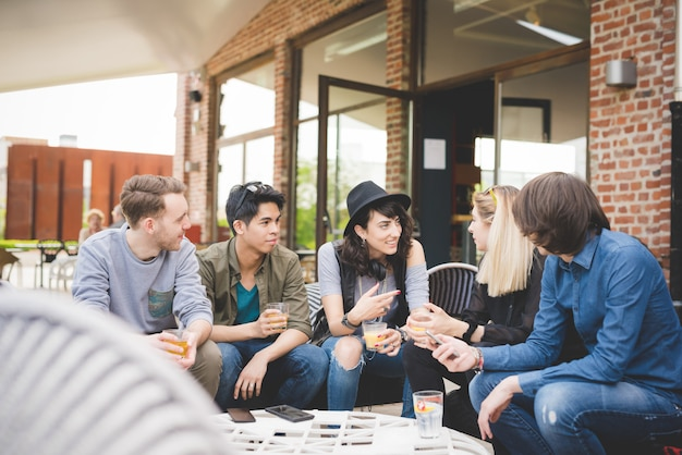 Grupo de jóvenes amigos multiétnicos sentado bar teniendo conversación