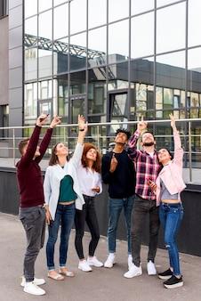 Grupo de jóvenes amigos de pie en la calle apuntando hacia arriba frente a un edificio moderno