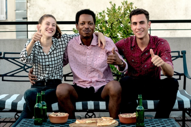 Grupo de jóvenes amigos con pizza y botellas de bebida.