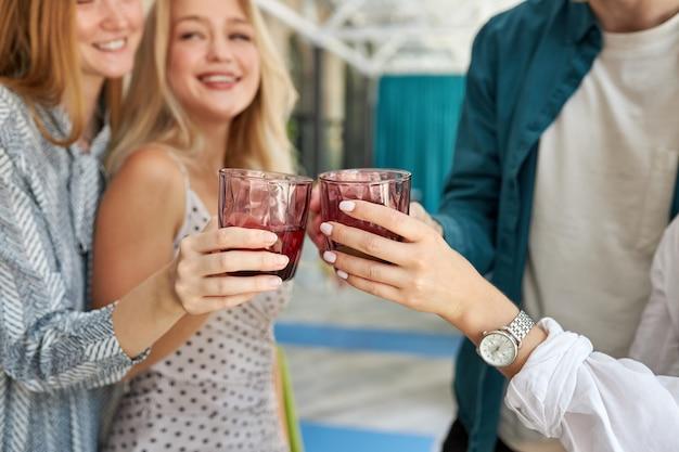 Grupo de jóvenes amigos tintineo de vasos con bebidas en el café