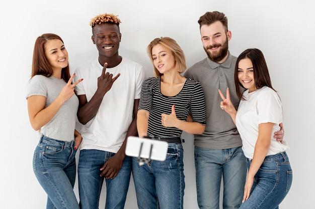 Grupo de jóvenes amigos tomando selfies