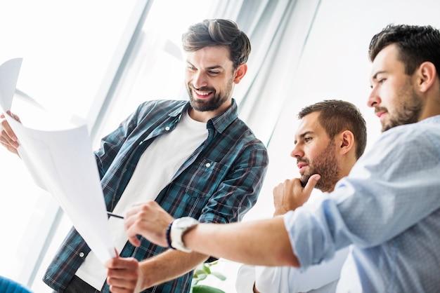 Grupo de jóvenes arquitecto masculino analizar plan