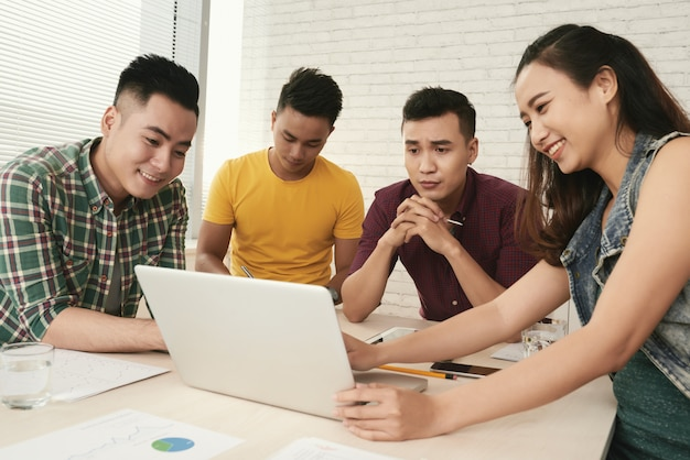 Grupo de jóvenes asiáticos casualmente vestidos de pie alrededor de la mesa y mirando la pantalla del portátil