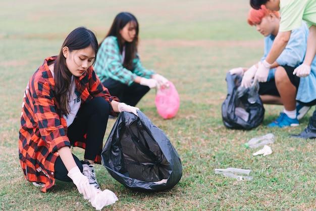Un grupo de jóvenes asiáticos están limpiando basura plástica en parques
