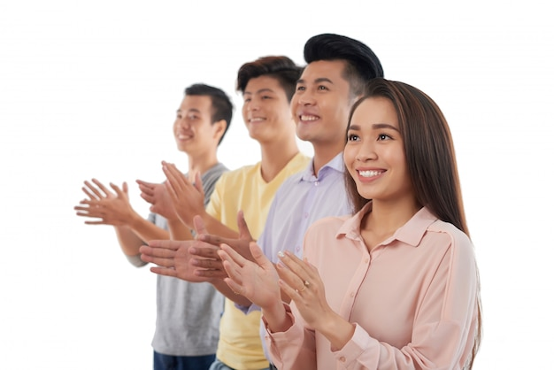 Grupo de jóvenes asiáticos de pie en fila y aplaudiendo