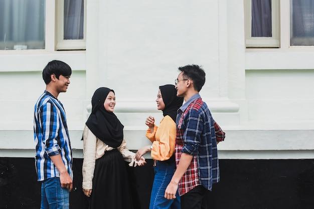 Grupo de jóvenes asiáticos sonriendo y hablando juntos