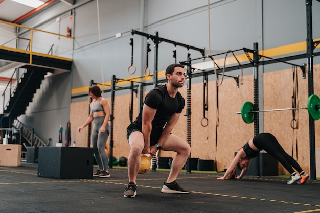 Un grupo de jóvenes atletas en un gimnasio de crossfit haciendo una variedad de rutinas de ejercicio mientras el entrenador y otros miembros del grupo los animan
