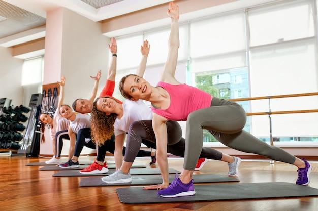 Grupo de jóvenes atractivos deportivos practicando clases de yoga con instructor, de pie juntos en ejercicio, ejercicio, longitud completa