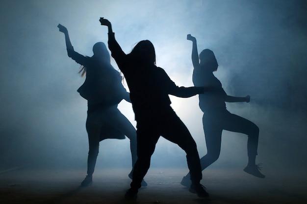 Grupo de jóvenes bailarinas en la calle por la noche.