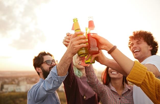 Grupo de jóvenes bebiendo cerveza y relajándose juntos en la azotea
