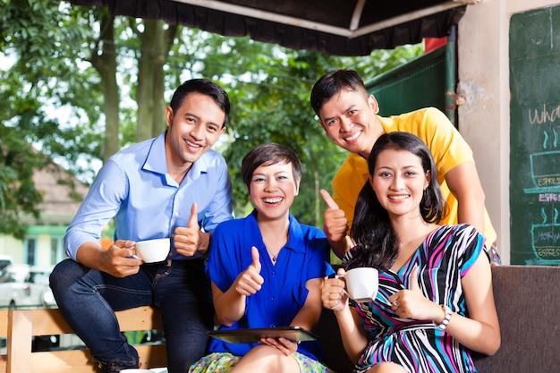 Grupo de jóvenes en una cafetería asiática.