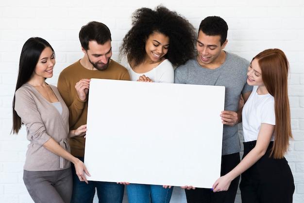 Grupo de jóvenes con un cartel juntos