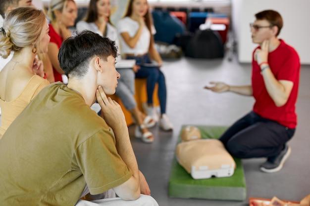 Grupo de jóvenes caucásicos aprendiendo cómo mantener una vida segura sentados juntos