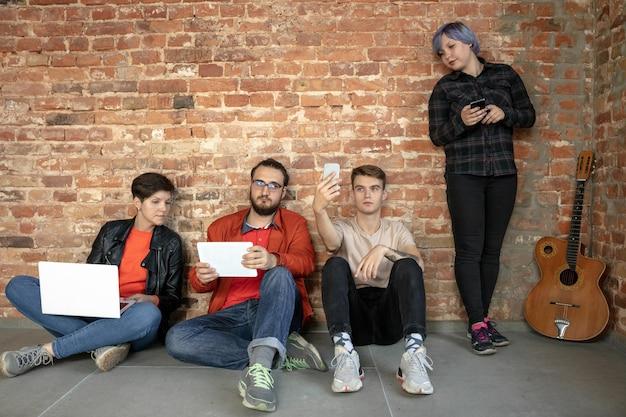 Grupo de jóvenes caucásicos felices detrás de la pared de ladrillo. compartir noticias, fotos o videos desde teléfonos inteligentes, computadoras portátiles o tabletas, jugar y divertirse. redes sociales, tecnologías modernas.