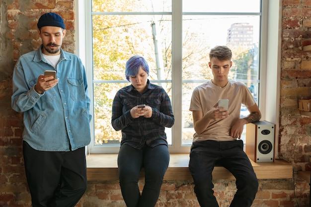 Grupo de jóvenes caucásicos felices de pie detrás de la ventana. compartir noticias, fotos o videos desde teléfonos inteligentes, grabar voz o jugar y divertirse. redes sociales, tecnologías modernas.