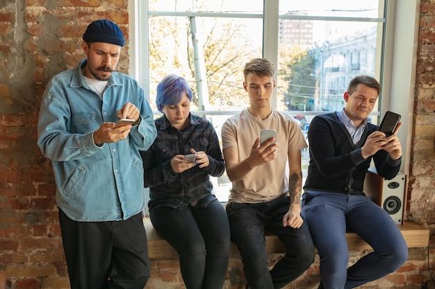 Grupo de jóvenes caucásicos felices de pie detrás de la ventana. compartir noticias, fotos o videos desde teléfonos inteligentes, hablar o jugar y divertirse. redes sociales, tecnologías modernas.