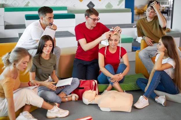 Grupo de jóvenes caucásicos practican el tratamiento de un paciente con vendajes