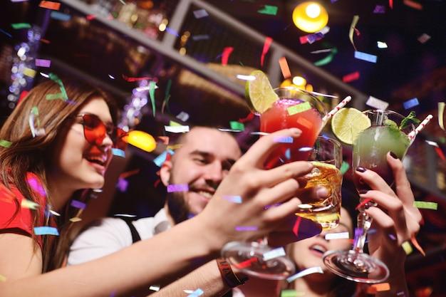 Grupo de jóvenes celebra un cumpleaños o navidad en una discoteca y saluda a su confeti