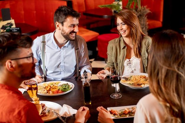 Grupo de jóvenes cenando en el restaurante