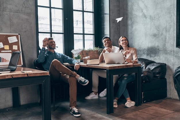 Grupo de jóvenes compañeros de trabajo juguetones en ropa casual elegante sonriendo y lanzando aviones de papel