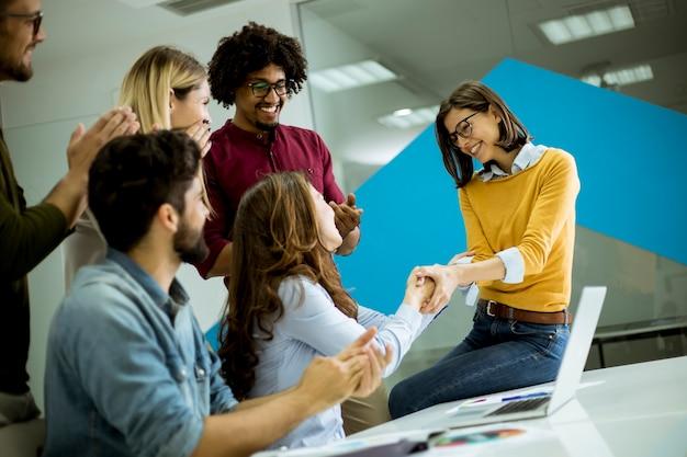 Grupo de jóvenes compañeros de trabajo que interactúan alrededor de una mesa y un apretón de manos en la oficina