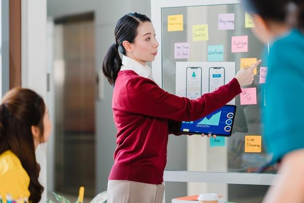 Grupo de jóvenes creativos de asia reunidos intercambiando ideas realizando ideas de presentación de negocios colegas de proyectos de diseño de software de aplicaciones móviles en la oficina moderna. concepto de trabajo en equipo de compañero de trabajo