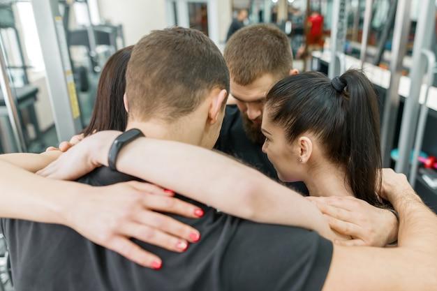 Grupo de jóvenes deportistas abrazándose juntos en el gimnasio