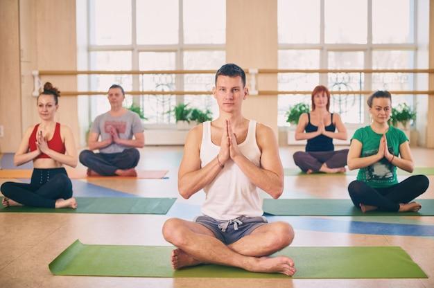 Grupo de jóvenes deportistas practicando clase de yoga con instructor, sentado en ejercicio de padmasana, postura de loto con las manos juntas en namaste