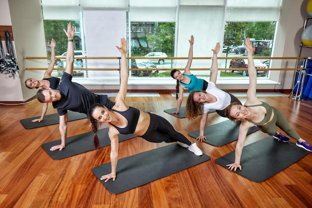 Un grupo de jóvenes deportistas en ropa deportiva, en un gimnasio, haciendo flexiones o planchas en el gimnasio. concepto de condición física grupal, ejercicios grupales, motivación