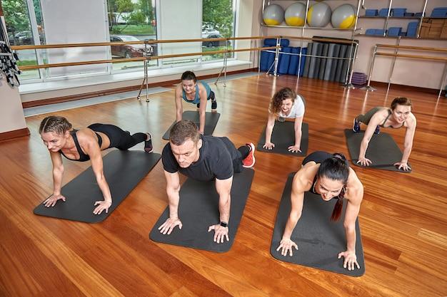 Un grupo de jóvenes deportistas en ropa deportiva, en un gimnasio, haciendo flexiones o planchas en el gimnasio.